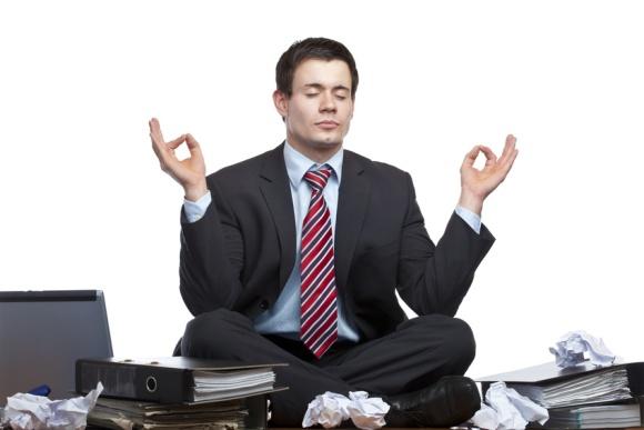 Gestresster, frustrierter Geschäftsmann meditiert im Büro auf Schreibtisch